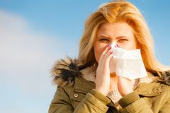 Sneezing woman into handkerchief, outside sunny shot Royalty Free Stock Images