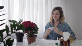 Seasonal flu, young beautiful woman suffers an allergic reaction and constantly sneezes and wipes her nose with napkin. Seasonal flu, a young beautiful woman stock video footage