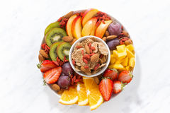 Seasonal fresh fruit on a plate and cereal flakes, top view Stock Photos