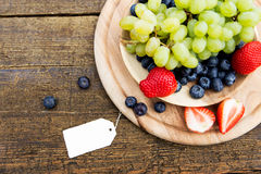 Seasonal fresh fruits in a bowl on wooden table, sign with copys Royalty Free Stock Images