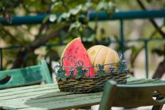 Seasonal fresh fruits, watermelon and rockmelon in basket on garden table Royalty Free Stock Image