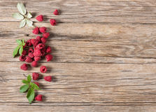 Seasonal fresh raspberry. Top view of fresh organic raspberry with green leaves on old wooden background  with copy space Royalty Free Stock Photography
