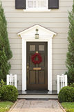 Seasonal Front Door of a Home. View of a dark front door with a red season wreath, greenery on the sides and view of the porch. Vertical shot Stock Image
