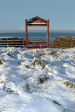 Seasonal frost covered framed red bench sea view Stock Photo