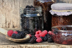 Seasonal fruit for jam. Blackberry and raspberry with glass jars on wooden background Stock Photography