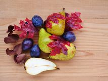 Seasonal fruits, pears, plums and fall leaves over wooden table. Autumn background with seasonal fruits, pears, plums and fall leaves over wooden table stock photography