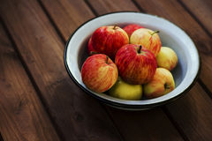 Seasonal garden red apples in metal bowl on wooden background Stock Photography