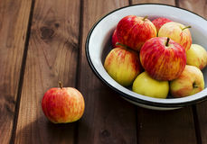 Seasonal garden red apples in metal bowl on wooden background Royalty Free Stock Photo