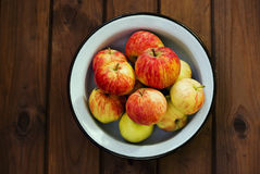 Seasonal garden red apples in metal bowl on wooden background Stock Image