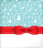 Seasonal greeting card with ribbon. Seasonal greeting card with delicate spherical ornaments each containing a traditional Christmas symbol decorated with a red Royalty Free Stock Image