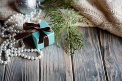 Seasonal holiday decor blue gift box wood texture. Seasonal holiday decor on wooden background. blue gift box with chocolate brown ribbon bow juniper twig and stock photo