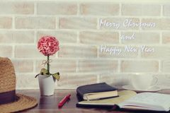 Merry Christmas and Happy New Year picture. Seasonal and holiday scenery brick wall, flower, book, a cup of coffee Stock Images