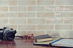 Merry Christmas and Happy New Year picture. Seasonal and holiday scenery brick wall, flower, book, a cup of coffee, old camera Royalty Free Stock Image
