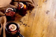 Seasonal and holidays concept Christmas mulled wine with beautiful orange slices inside the glass , covered with warm white scarf stock photography