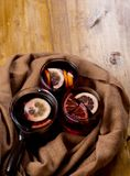 Seasonal and holidays concept Christmas mulled wine with beautiful orange slices inside the glass , covered with warm white scarf stock images