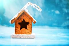 Seasonal and holidays concept. Decorative house toy on a blue ice winter background. Selective focus.  Stock Image