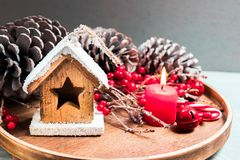 Seasonal and holidays concept. Decorative toy house, candle, fir cones, winter background. Selective focus. Seasonal and holidays concept. Decorative toy house Stock Images