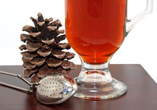 Seasonal Hot Tea And Strainer Close Up. Close up of seasonal scene of a glass mug of tea, tea strainer and pine cone on a white background royalty free stock photos