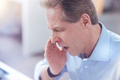 Unhappy ill man sneezing. Seasonal infection. Unhappy sad ill man covering his mouth and sneezing while having seasonal infection Royalty Free Stock Images
