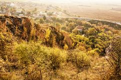 Seasonal natural outdoors scene. – rocks, colorful trees, village, road and fields. Vibrant colors. Beauty in nature. Yellow photo filter royalty free stock image