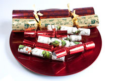 Seasonal Offering. A red charger plate piled with traditional Christmas crackers Stock Images