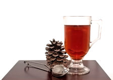 Seasonal Pine Cone Tea Scene. Seasonal scene of a glass mug of tea, tea strainer and pine cone on a dark wood table royalty free stock images