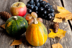 Seasonal pumpkin on a table with autumn leaves, closeup Royalty Free Stock Image