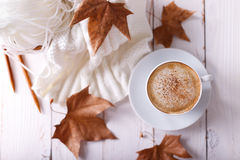 Seasonal relax concept. Hot coffee cappuccino, knitted blanket and autumn leaves on old wooden background. Seasonal relax concept Royalty Free Stock Images