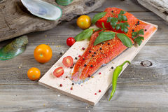 Seasonal Salmon prepared for cooking. Horizontal view of raw red salmon, skin side down, on maple wood grilling plank with seasoning and other herbs surrounded Royalty Free Stock Photos