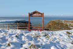 Seasonal snow covered framed red bench sea view Royalty Free Stock Photos
