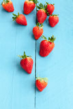 Seasonal strawberries on blue wooden background Stock Photography