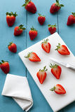 Seasonal strawberries cutted on blue and white wooden background Royalty Free Stock Photo