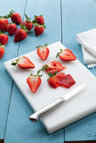 Seasonal strawberries cutted on blue and white wooden background Stock Photo
