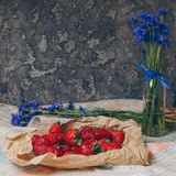 Seasonal summer flowers blue cornflowers and fruits strawberries on a napkin close-up conceptual background stock image
