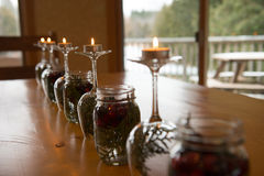 Seasonal Tea light Table Centre Piece. Focus on Tea lights decoratively designed on top of upside down Wine Glasses that are filled with Cedar clippings. As well royalty free stock images