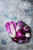 Seasonal winter autumn purple vegetables over gray stone table. Plant based vegan or vegetarian cooking concept. Clean eating food. Seasonal winter autumn purple stock photos