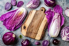 Seasonal winter autumn purple vegetables over gray stone table. Plant based vegan or vegetarian cooking concept. Clean eating food. Alkaline diet stock image