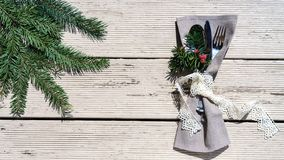 Seasonal winter table setting with white lace ribbon and gray textile with green branch fir tree on white wooden background. Happy royalty free stock photo