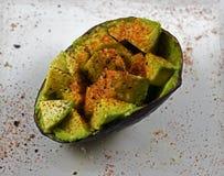 Seasoned avocado half. Raw avocado half seasoned with pepper, salt and paprika on a white dish Royalty Free Stock Photo