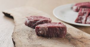 Seasoned raw beef fillet for steak on wooden board. Wide photo Royalty Free Stock Images