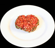 Seasoned raw red hamburger on white plate Royalty Free Stock Images