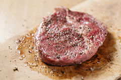 Seasoned raw rib eye steak on board closeup Stock Photography