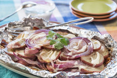 Seasoned red potatoes and onions grilled with bacon Stock Photography