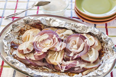 Seasoned red potatoes and onions grilled with bacon Stock Image