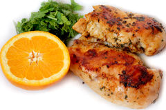 Seasoned roast chicken with orange and green. Roast chicken and half orange with parsley and dill Royalty Free Stock Image