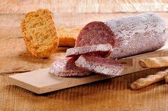 Seasoned salami and grissini Stock Photos