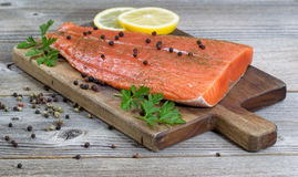 Seasoned Salmon Fillet on rustic wood Stock Photo
