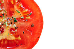 Seasoned tomato slice. Mouth watering seasoned tomato slice with details on sea salt and herbs on white background Royalty Free Stock Photo