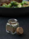 Seasoning. Close up view of small bottle with Italian seasoning on gray background Stock Photos