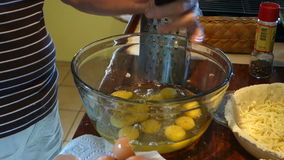 Seasoning cracked eggs before whisking stock footage